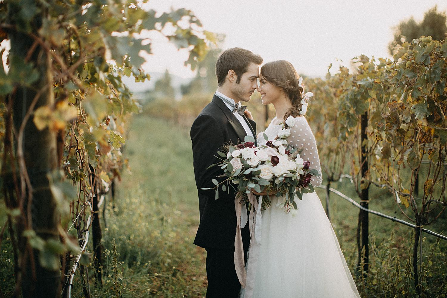 Bride and groom standing in grape plantation