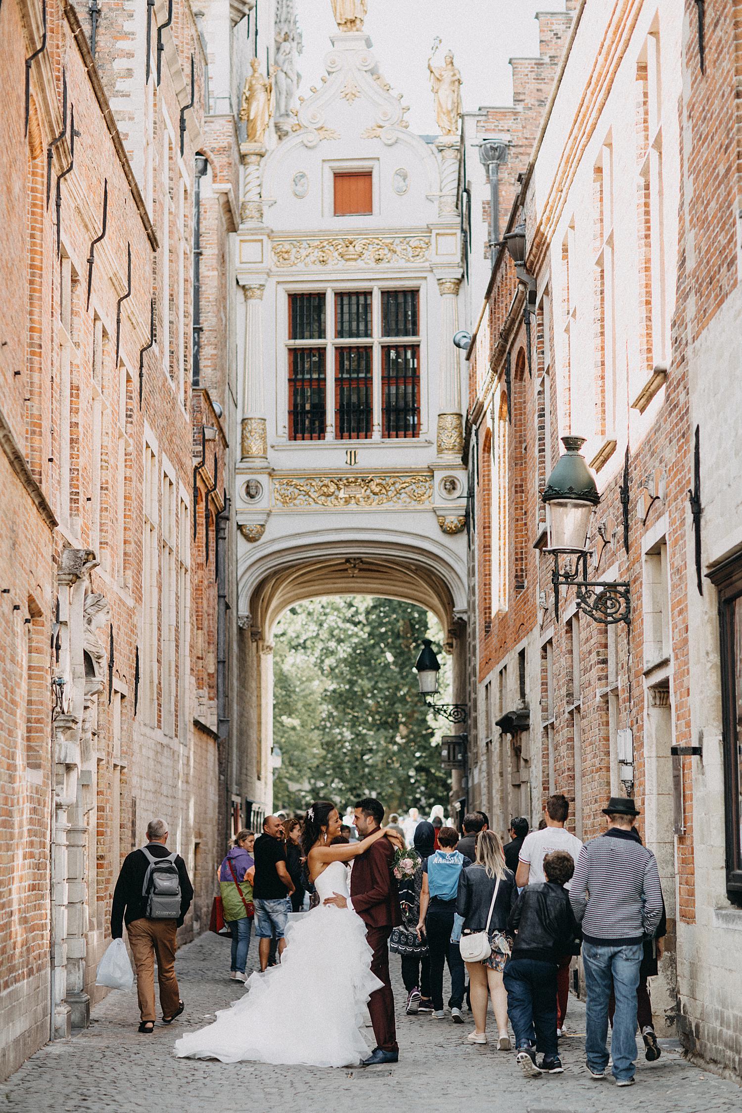 Bruidspaar poseert in oude drukke straat Brugge