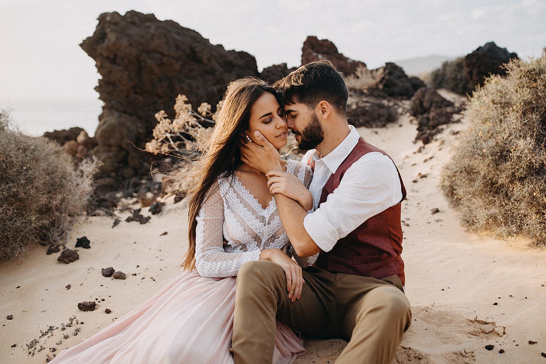 Bride groom sitting in sand beach La Graciosa