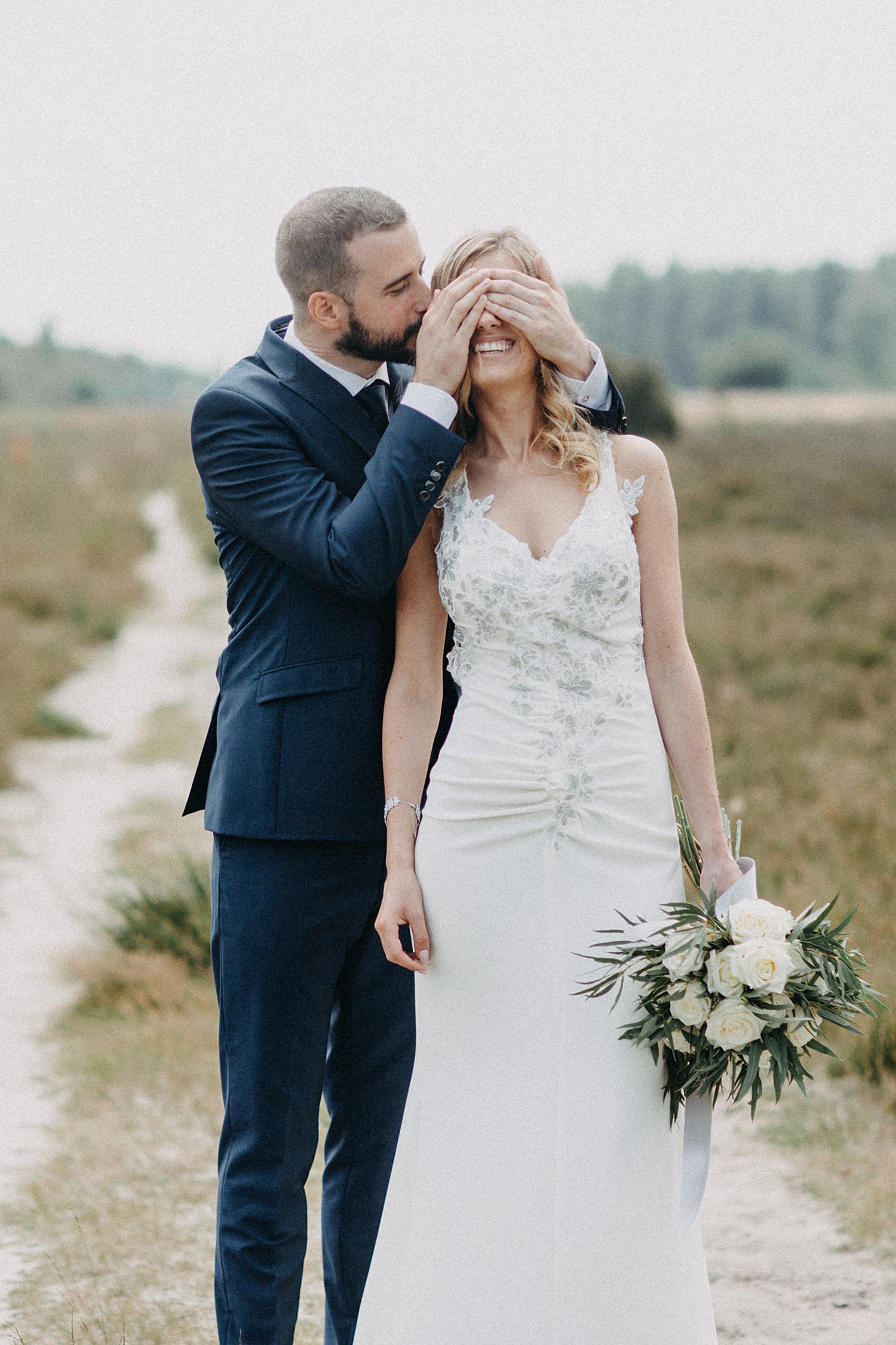 bruidegom dekt ogen af huwelijksreportage Lommelse heide