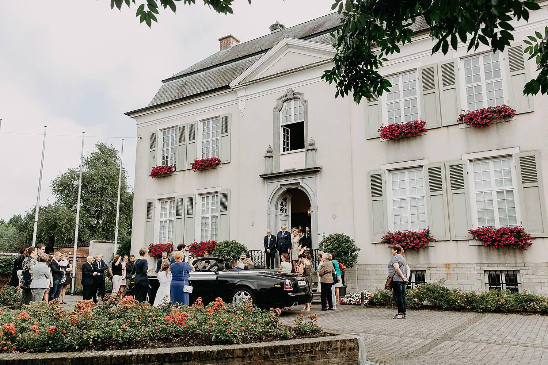 bruidspaar met bruidswagen voor gemeentehuis