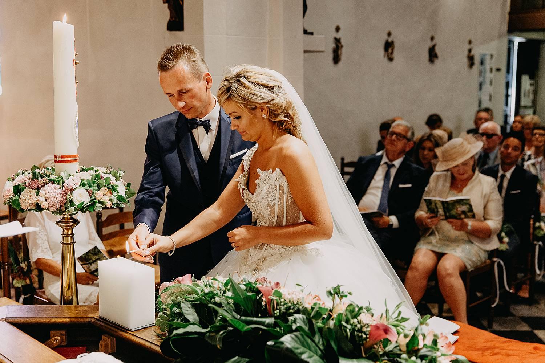 bruidspaar steekt paaskaars aan in kerk