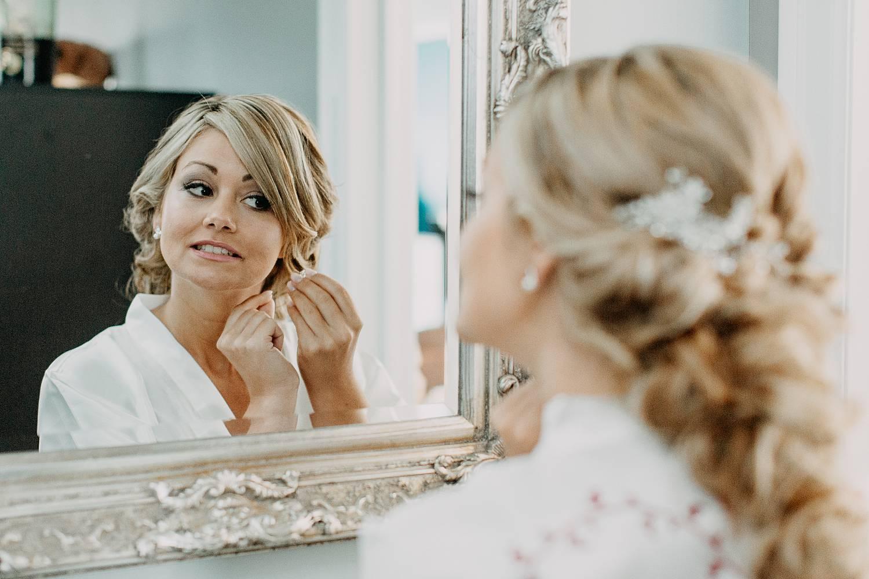 Ma-up bruid kijkt in spiegel