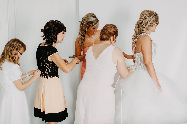 Vriendinnen helpen bruid met dichtknopen jurk