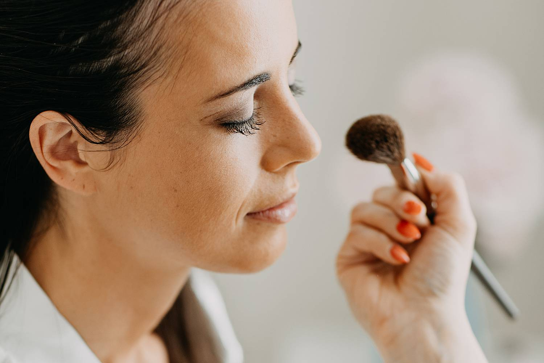 Make-up artiest brengt make-up aan bruid