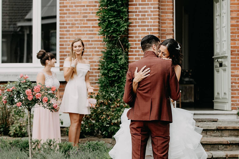 Intrede huwelijk voordeur knuffel bruidspaar
