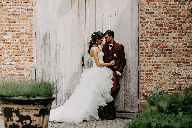 De Barrier huwelijksreportage bruidspaar tegen houten deur