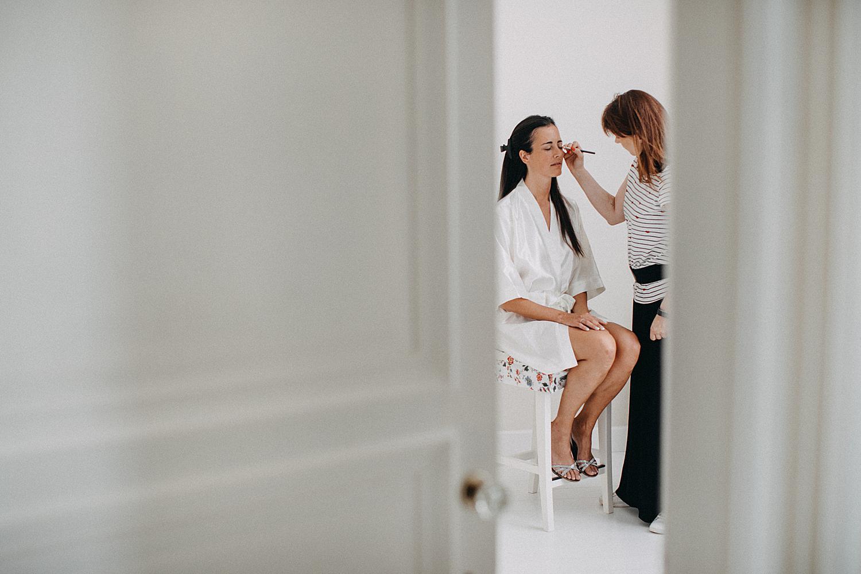 make-up artiest brengt schmink aan bruid