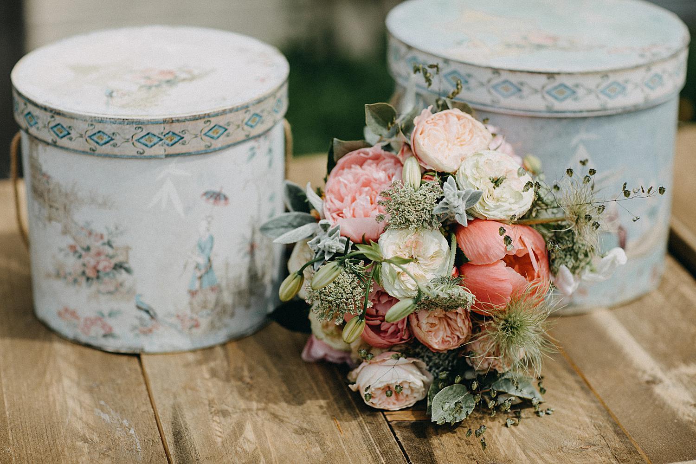 bruidsboeket op houten tafel met twee versierde ronde dozen