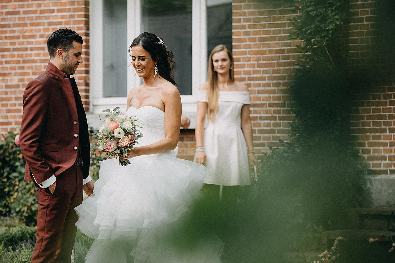 bruidegom geeft bruidsboeket first look tuin