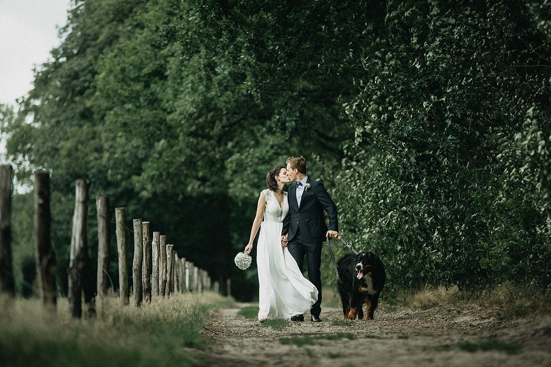 bruid en bruidegom wandelen in dreef Kiewit met hond