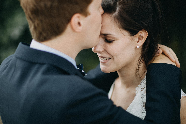 bruidegom geeft bruid kus voorhoofd
