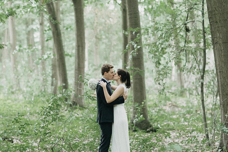 bruid bruidegom kussen in loofbos Kiewit
