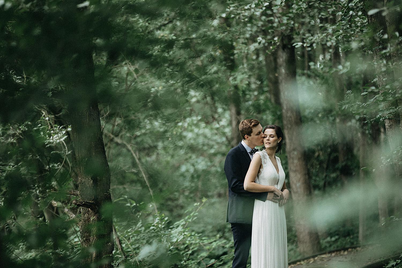 bruid en bruidegom kussen in bos Kiewit
