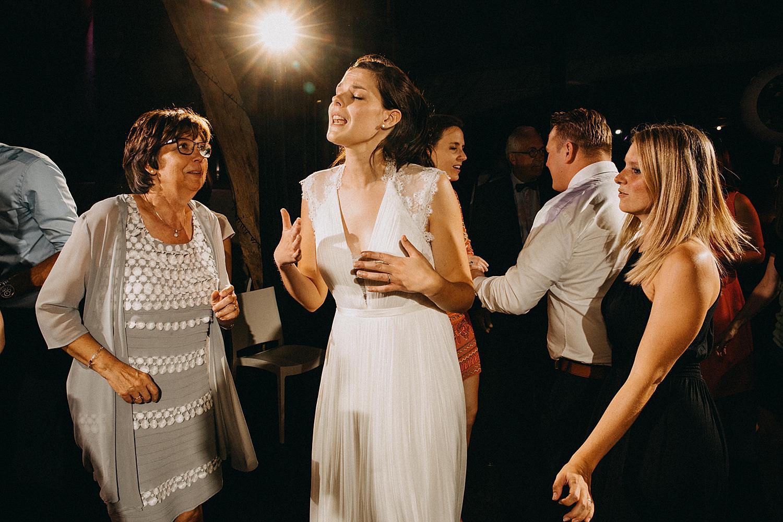 trotse moeder kijkt naar bruid op dansvloer tijdens dansfeest huwelijk