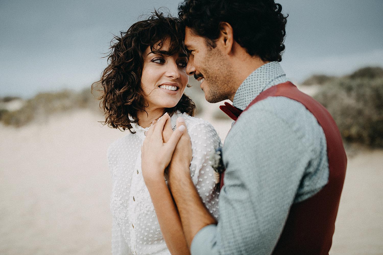 groom and bride hug on beach