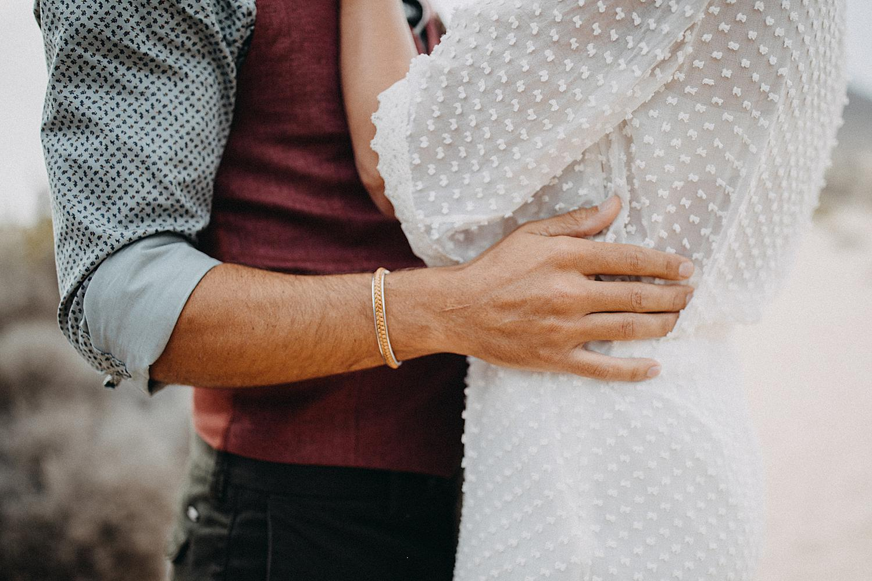 detail of hand groom on weddingdress