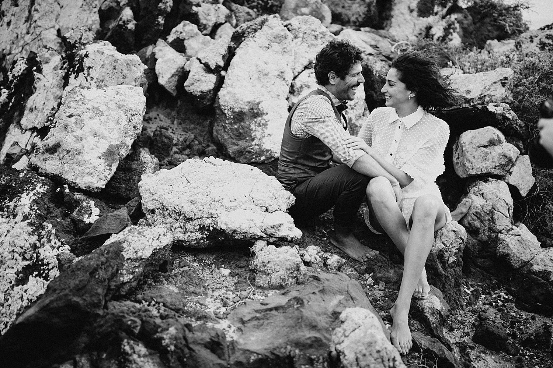 bride and groom sitting on rocks beach