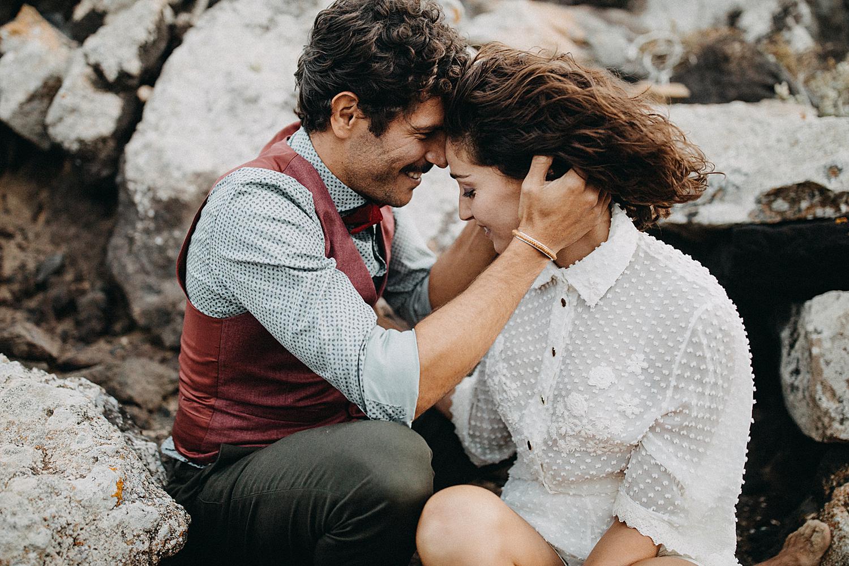 bride and groom hug on rocks beach