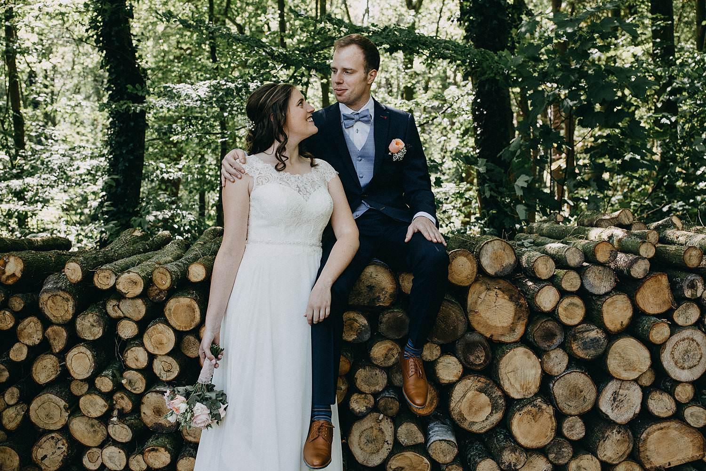 Sterrebos huwelijksreportage bruidspaar voor gekapte boomstronken