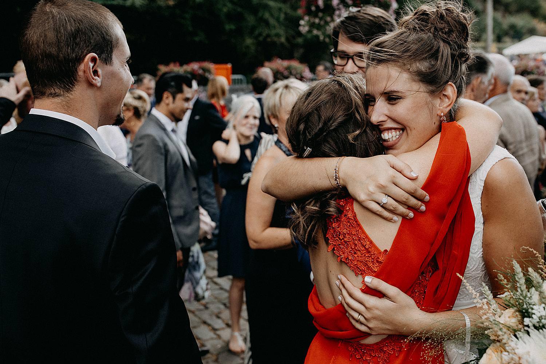 bruid omhelst vriendin buiten kerk Vlaamse Ardennen