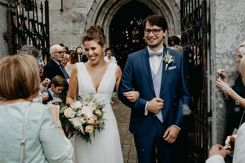 bruidspaar arm in arm buiten kerk Aywaille