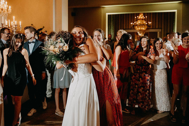 vriendin vangt bruidsboeket tos feestzaal De Kleine Graaf