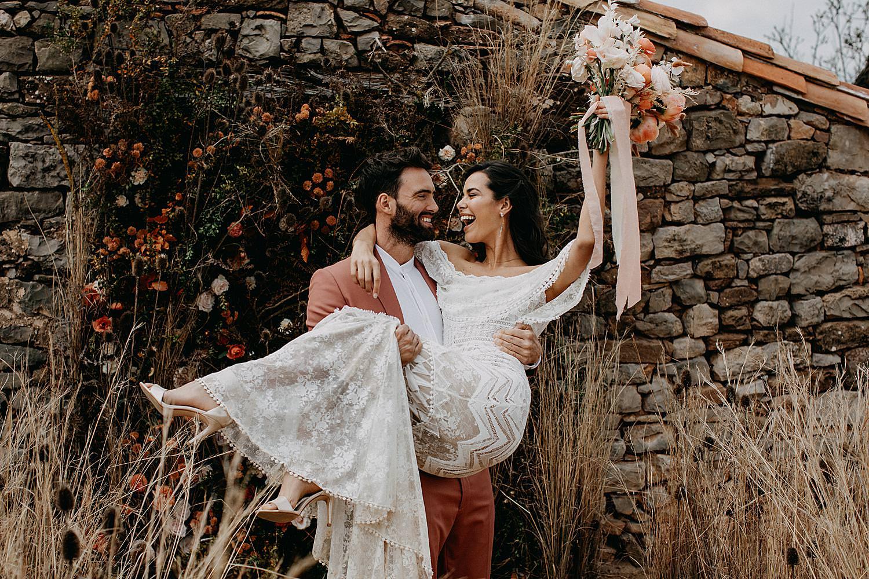 Barcelona bruidegom draagt bruid in armen met bruidsboeket