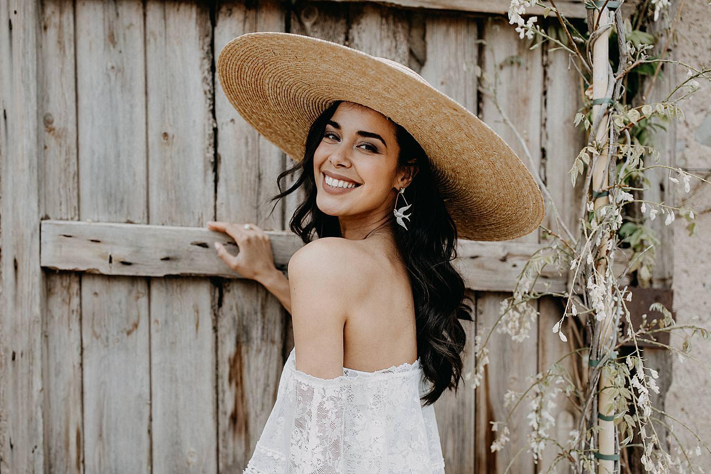 bruid met stro hoed voor houten poort