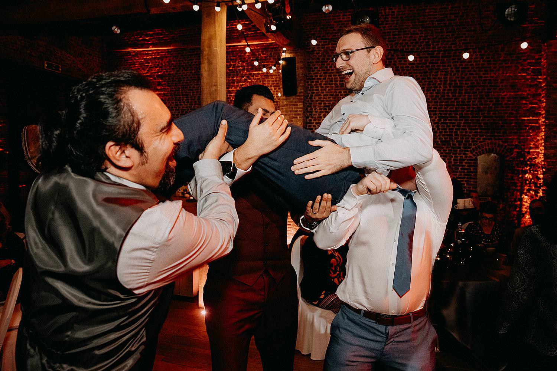 gasten tillen vriend op dansvloer huwelijk
