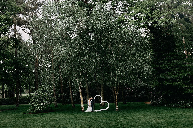 bruidspaar poseert langs wit hart decoratie