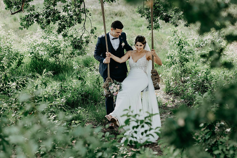 bruidspaar op schommel onder boom