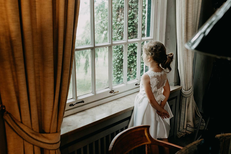 bruidsmeisje kijkt door kasteelraam