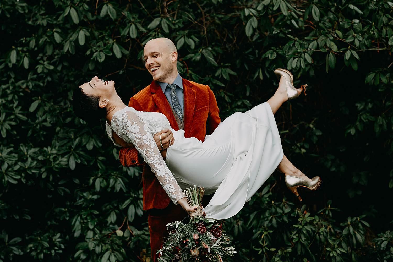 Bruidegom draagt bruid winterhuwelijk
