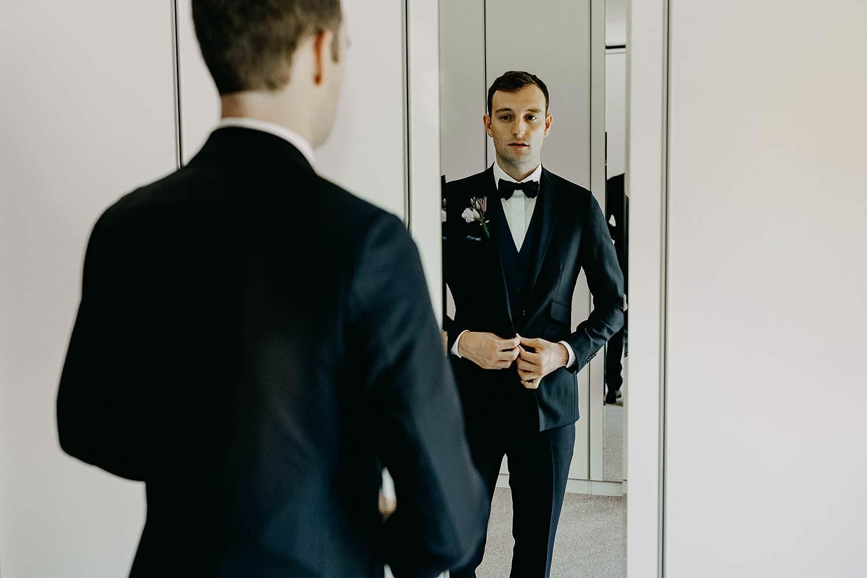 Aankleden bruidegom dichtknopen vest