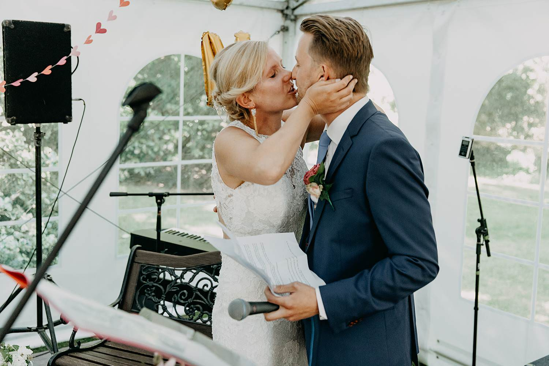 Binnenceremonie huwelijk witte tent bruidspaar kust