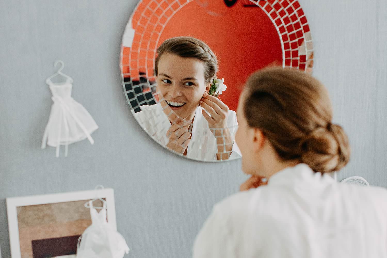 Bruid aanbrengen oorringen in spiegel