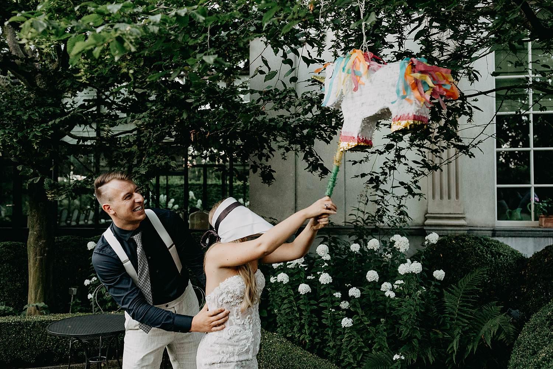 bruid slaat pinata onder boom