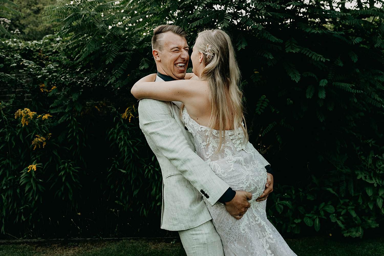 bruidegom draagt bruid tuin feestzaal