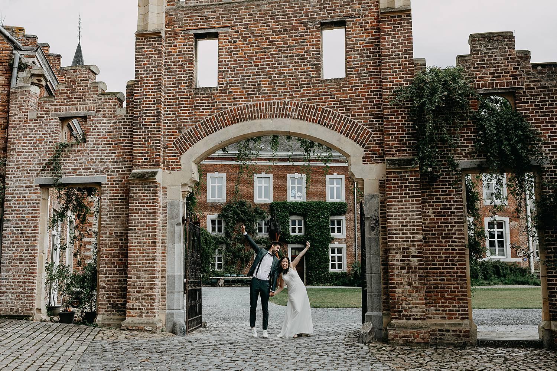 Bruidspaar onder stenen poort Kasteel Nieuwenhoven