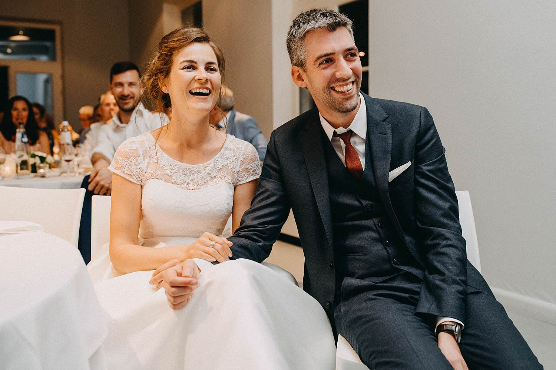 Bruidspaar kijkt voorstelling vrienden huwelijk