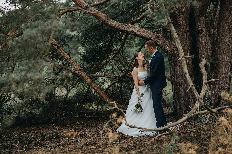 De Teut bruidspaar poseert voor sparren