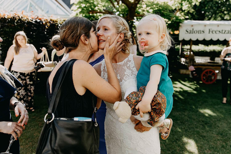 De Venkel huwelijk buitenreceptie bruid groet familie met baby op haar arm