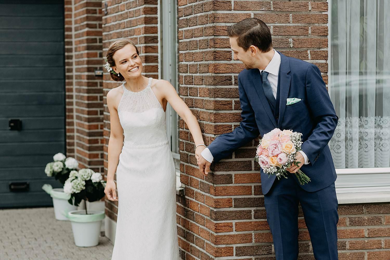 First look huwelijk bruid en bruidegom rond hoek van huis
