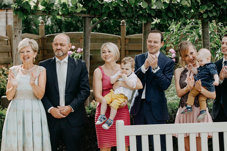 First look huwelijk in tuin familie kijkt toe