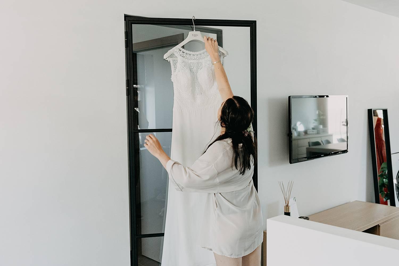 Herk De Stad bruid neemt bruidsjurk van spiegel