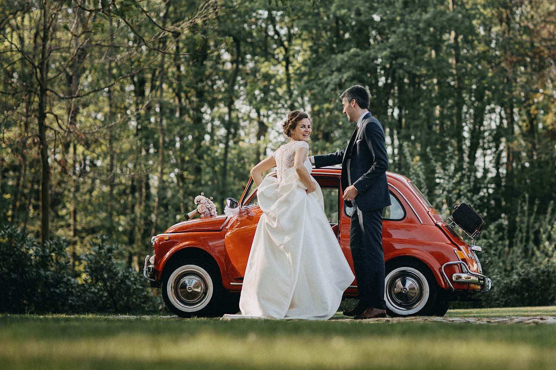Hof ten Laere huwelijk bruidspaar voor rode bruidswagen fiat 500