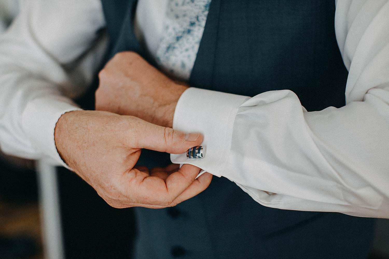 Huwelijk voorbereiding bruidegom dichtknopen hemdsmouwen