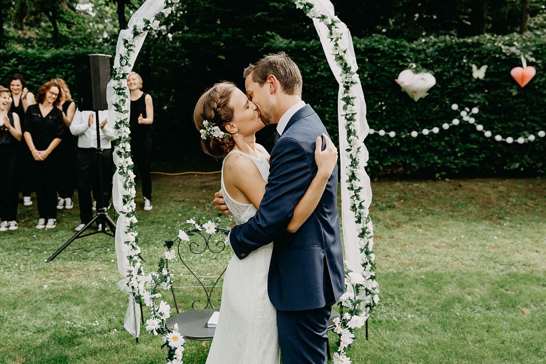Keienhof grote buitenceremonie bruidspaar kust onder plantenboog