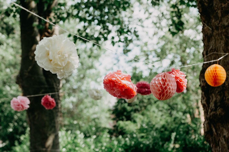 Kiezelhuys buitenceremonie huwelijk slingers met papieren bloemen